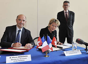 Pierre Moscovici and and Eveline Widmer-Schlumpf, Federal Councillor, Head of the Federal Department of Finance of the Swiss Confederation sign a tax treaty on 11th July 2013.