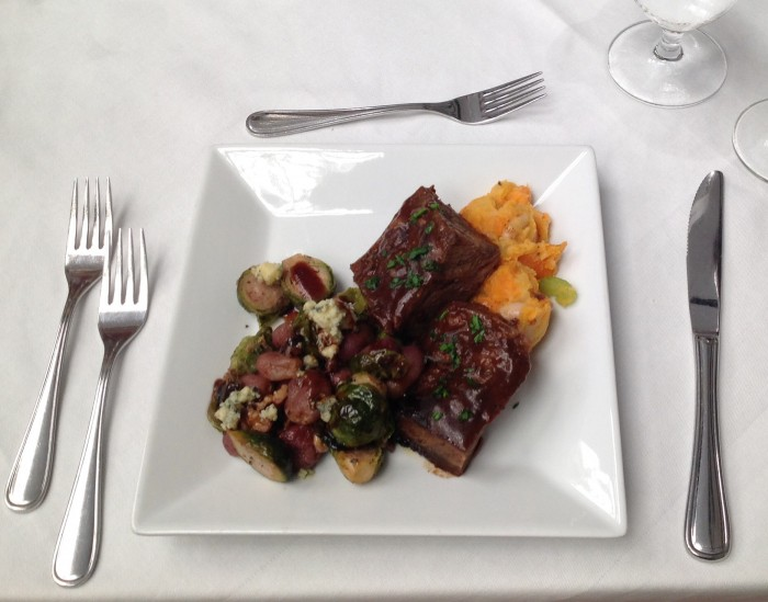 Savory Short Ribs Served Over White Bean Veggie Mash-up accompanied by Roasted Brussels Sprouts and Concord Grapes with Blue Cheese and Walnuts